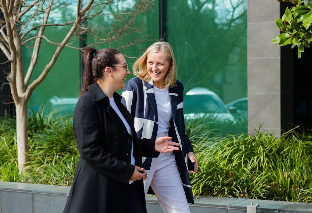 Two people enjoying a walking meeting outside building