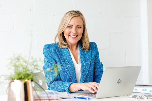 Wendy Cole Sitting at Desk with laptop being productive
