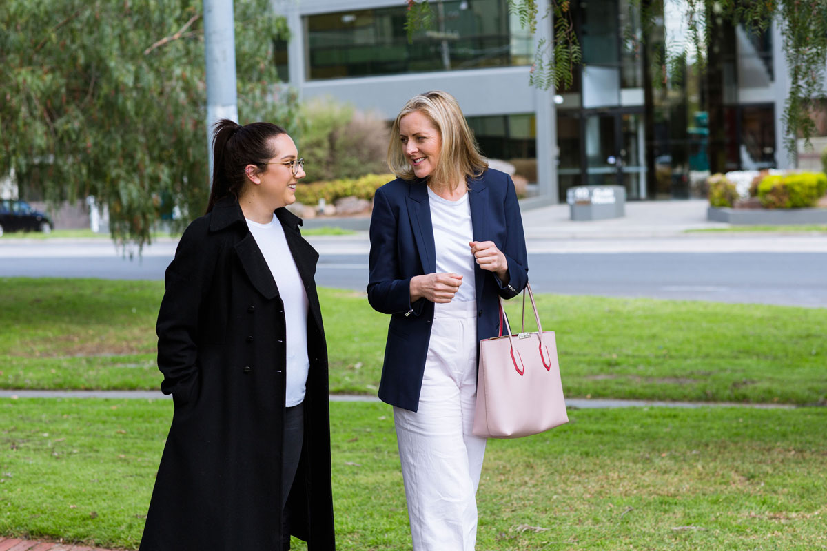 two executives on a walking meeting talking about leader as coach training