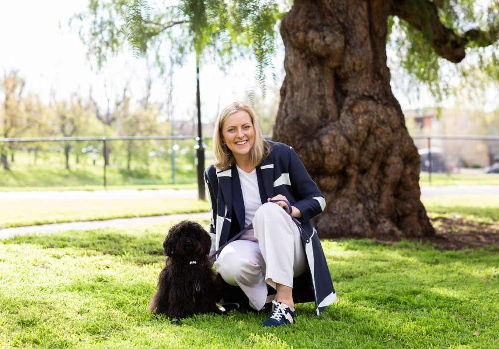 Wendy Cole and her dog Lulu on grass in front of big tree